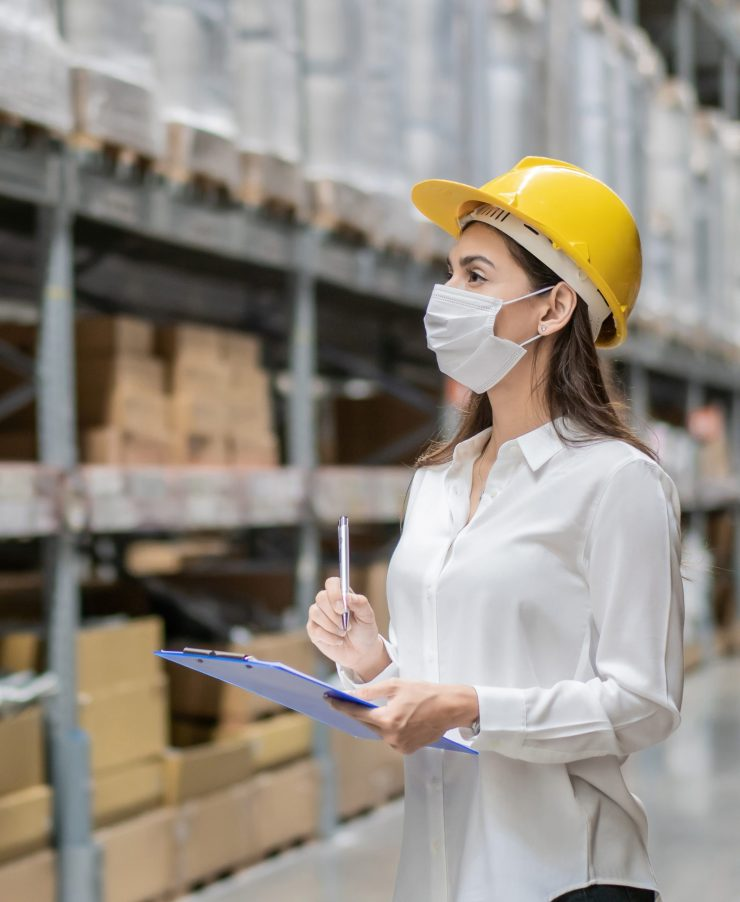 Female construction worker wearing protective face mask writing on clipboard checking product on aisle in warehouse factory. industrial social responsibility prevention Coronavirus. new normal working